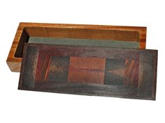 """Handmade box by J. Seaton with a lid of African pink ivorywood, cocobolo, black palm, wenge, purpleheart, and mahogany. The body is made from wenge and is 1 1/2""""D. Each box is completely handmade using rare and exotic woods. Each is created spontaneously and no two are ever exactly alike. Each is sanded seven times to a satin smooth surface and finished in an oil and wax finish.  Size: 12 3/4""""L x 5""""D x 2 1/2""""H  Price: $425.00  -- on ScrimshawGallery.com #woodworking #jewelrybox"""