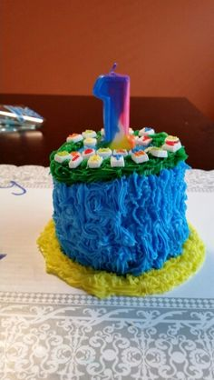 Edward's first birthday cake, smash cake decorated in blue, green and yellow icing and it's a 3 tier 6 inch cake