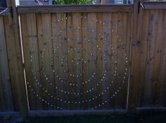 Montessori natural outdoor space: Spiral Fence Marbles - Drill smaller holes all the way through, then larger holes for the marbles that don't go all the way through fence so the marbles are countersunk on one side. The marbles won't fall through the fence. It looks beautiful when the sun shines through.