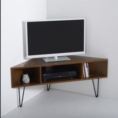 """The vintage look is undoubtedly back and this sleek corner unit follows the trend to a T. In a deep walnut finish and 3 V-shaped legs, attention to the retro trend is seriously sharp.Designed for practicality with 3 storage compartments - 1 for a DVD player and 2 smaller compartments for other accessories.Complete with cable access holes and space for up to 50"""" TVs, this is the perfect way to house your devices.3 compartments (1 large compartment for DVD player and 2 small compartment..."""