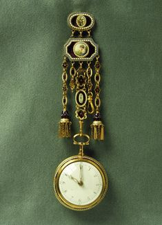 Gold chatelaine and case watch: late 18th century.  The chatelaine has a large gilded brass hook and each of its hangers has a gilded brass backing. In the centre an oval cartouche contains a painted enamel of a bird on a branch with a border of white enamel dots around the outside.