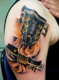 Stunning guitar tattoo on the arm. The details of the tattoo are simply stunning as you can see a hand strumming the guitar as if it's coming to life.
