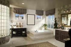 Bathroom with step-up soaker tub, two sinks, rug and glass-tile shower