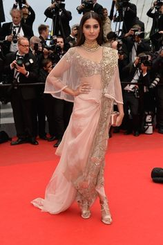 Sonam Kapoor in Anamika Khanna Another memorable look from 2014 - Sonam Kapoor made wowed at the Cannes Film Festival in this stunning soft pink saree and that stunning jadau necklace. The loose draping style and the cape add a contemporary touch to the ensemble and would be perfect for a reception outfit! Indian bride - Indian wedding - Indian designer - Bollywood wedding - Indian couture #thecrimsonbride
