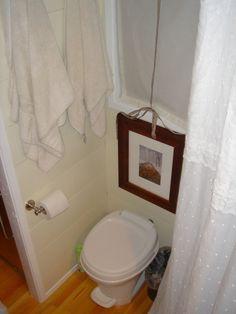 derek's tiny house toilet, towels hanging, shower curtain, bathroom window and door