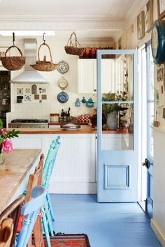 I love the country cottage vibe this kitchen has going on, especially with the mismatched chairs and the blue door and floor! Such a great color.