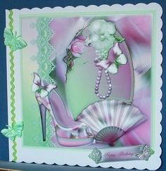 Magnolia Shoe in green and pink tones card topper on Craftsuprint designed by Julie Hutchings - made by Cheryl French - Printed onto glossy photo paper. Attached base image to one side of 8x8 scalloped edged card stock using ds tape. Built up image with 1mm foam pads. Added green ric-rac ribbon to side and some fabric butterflies. - Now available for download!
