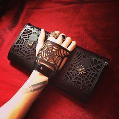 Handmade leather clutch by Perrin with spiderweb cut outs and spiders.