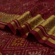 #PadmaPaaduka #Handwoven Arakku Red Patola Silk Sari with Golden Border ~ Sometimes all it takes is a beautiful colour to make life enchanting. This arakku red looks glorious with the diamonds #Motifs and the thin #Ikkat diagonal lines. Nothing but that golden tissue border is needed to make this a masterpiece! Code No. 530511728