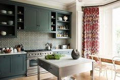 We love the combination of colors created with this kitchen's stunning tile backsplash, bold drapery, and deep-green cabinetry. The fun ikat print on the luxurious drapes soften the bold, geometric backsplash, making the space feel cozy rather than jarring.