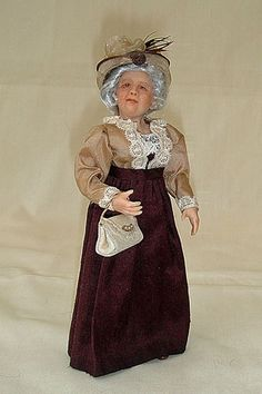 Victorian Lady dressed in brown skirt, coffee coloured blouse with cream lace trimmings, completed with a cream straw hat.