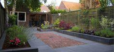 Strakke betontegels 60x60cm gecombineerd met nieuw gebakken klinkers. De borders zijn gemaakt van strakke muurelementen!