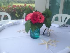 Floral centerpieces in blue mason jars made by Flowers in Vieques