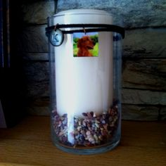 Candle, votive, pebbles. Leather cording with homecrafted wood charm and letter charm. Made for the loss of a pet