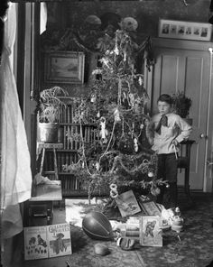 Young boy standing next to a #Christmas tree, ca 1900