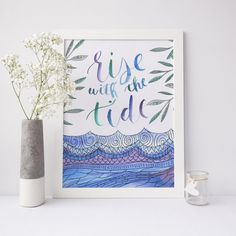 """Bring good vibes to your morning with this inspirational surfer quote print. It features the phrase """"rise with the tide"""" in a hand lettered watercolor text."""