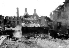 A Sherman M4A1 bulldozer clears the central bridge in Lonlay L'abbaye. This tank is from 66th Armored Regiment, 2nd Armored Division. Mid-August 1944.