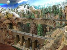 Nice bridge scene created by Jim Blattau, I love the mountains and trees in the background. #modeltrainsets