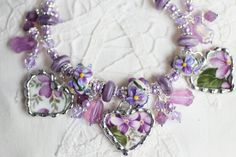 Broken China Bracelet, China Heart Charms, Handmade Lampwork Beads, Violet, Sterling Silver FlowerToggle Clasp. $96.95, via Etsy.