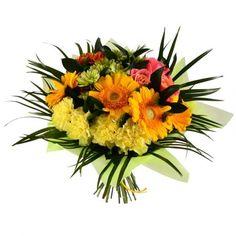 Яркая игривая композиция из оранжевых гербер, коралловых роз, зеленых и оранжевых хризантем и нежно-желтых гвоздик, украшенная листьями феникса и обернутая легким слоем декоративной бумаги светло-зеленого оттенка.