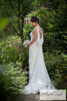 What a glamorous bride in a truly beautiful wedding dress enjoying some time in the graden!
