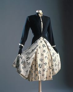 """Ensemble  House of Chanel  (French, founded 1913)  Designer: Gabrielle """"Coco"""" Chanel (French, Saumur 1883–1971 Paris) Date: ca. 1956 Culture: French Medium: silk, wool, leather Dimensions: Length at CB (a): 48 in. (121.9 cm) Length at CB (c): 48 in. (121.9 cm) Credit Line: Brooklyn Museum Costume Collection at The Metropolitan Museum of Art, Gift of the Brooklyn Museum, 2009; Gift of H. Gregory Thomas, 1959"""