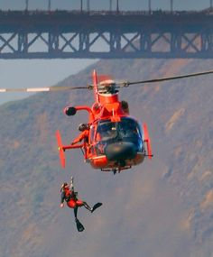 Vintage Helicopters Coast Guard Helo 6502 hoisting a Rescue Diver out of the San Francisco Bay with the Golden Gate Bridge in the background. Coast Guard Rescue Swimmer, Coast Guard Helicopter, Us Coast Guard, Military Helicopter, Military Aircraft, San Francisco Bay, Aigle Animal, Vintage Airplanes, Aircraft Design