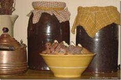 Primitive kitchen display.  I love the crocks covered in cloth