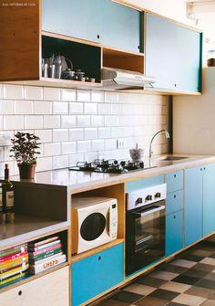Ladrilhos hidráulicos, subway tiles e marcenaria colorida na cozinha desse apê compacto.