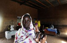 A southern Sudanese woman shows her inked finger after voting at a polling center in Khartoum on January 10, 2011. The historic vote created the world's newest nation as South Sudan gained independence. (Khaled Desouki/AFP/Getty Images) #