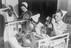 GAS DRILL AT A LONDON HOSPITAL: GAS MASKS FOR BABIES ARE TESTED, ENGLAND, 1940. Three nurses put on their gas masks, whilst a fourth nurse attends to the gas masks of two babies in the cot in front of her. Adults were told to put on their own gas mask before helping children or other adults with theirs.
