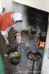 The two pale pink lidded pots at the hearth are reproduction large pipkins. See my blog for the source