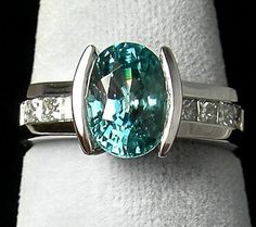 The AGTA Daily Gem:  A daily showcase of beautiful gemstones and jewelry from our AGTA Members!  Today's ring features a 4.27 ct. natural, oval-cut blue Zircon flanked by 1.0 ctw. princess-cut, channel-set Diamonds! Who wouldn't want to rock this custom-designed piece from D Gem Creations Studio?