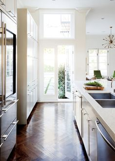 Kitchen with ivory shaker cabinetry, brass pulls, glass door refrigerator, herringbone wood floors