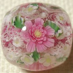 japanese lampworked beads with flowers encased in clear glass.