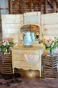 Cake displayed on an antique dresser with old doors and crates.