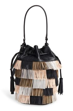 Tiered layers of fringe define this structured bucket bag. A top handle and an optional, adjustable shoulder strap add convenient carrying options.