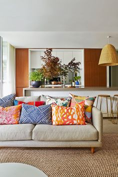 a beige and white contemporary living room gets a jolt of color by a bunch of throw pillows
