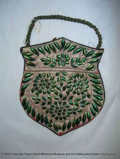 This bag is made of white silk satin and is decorated with applied green beetle wings. During the later part of the 19th century, there was a fashion for trimmings and detailing from nature. Real beetle wings, and sometimes the whole beetle, were used as decoration on bags.