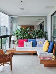 """LAYOUT 1 Varanda com sofá em """"L"""" desenhado sob medida com mesas laterais integradas."""