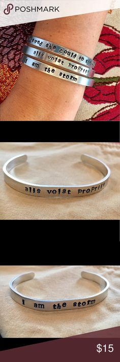"""Stamped silver cuff This hand stamped aluminum cuff is a small bracelet, but can have a huge impact with its powerful words. """"she believed she could so she did"""" // """"i am the storm"""" // """"alis volat propriis"""" // """"nevertheless, she persisted""""                                                                        You can also choose to customize your own bracelet with a quote, name, or label! Max 37 characters. 6mm wide, 14 gauge. Jewelry Bracelets"""