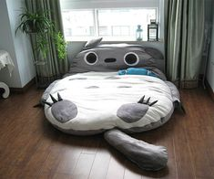 There is a Totoro bed! Somebody has made a My Neighbor Totoro bed, and for once the adorable cartoon coziness is not just for children. The cuddly, fuzzy, full-sized Totoro cushion bed is actually sized to accommodate two adults. Sure, many grown-ups would think twice about adopting this particular new friend, but it certainly has a leg up on most futons.