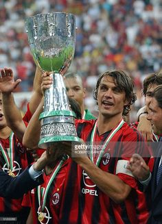 AC Milan captain Paolo Maldini (C) holds the trophy in celebration after winning the Italian SuperCup final match over Italian club Lazio at San Siro Stadium in Milan 21 Agust 2004. AC Milan won 3-0.
