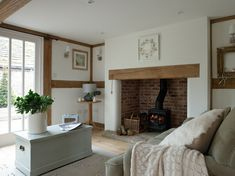 Holz Kaminofen mit Abzug und helle Farben im Wohnzimmer