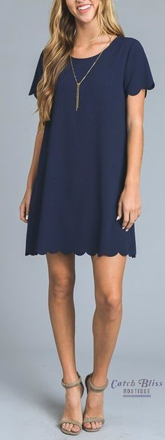 """The Sweet Embrace Navy Dress is definitely sweet! Scalloped detailing adorns the bottom hem and sleeves. Pair this party-ready dress with sky-high heels or flats for a head turning look. This Sweet Embrace Navy Dress is made from 98% Polyester, 2% Spandex and has short sleeves. This dress is made in the USA and the model is wearing a size small. Please hand wash cold. The length of a small is 33"""", a medium is 34"""" and a large is 35""""."""