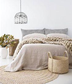 Chambre aux tons naturels avec le linge de lit en lin, tapis en rotin, table de chevet en bois et gros plaid pour une ambiance cocooning
