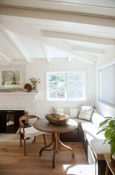 white painted beamed ceilings above modern dining nook with banquette and wood table and chairs / sfgirlbybay