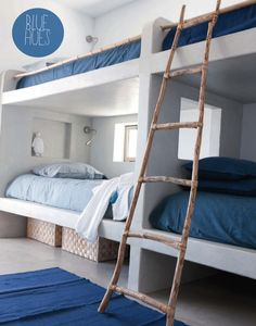gorgeous built-in bunks . wood . baskets . blue . lamps . little window to ouside and in between beds .