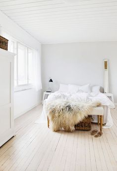 White bedroom with whitewashed floors and faux fur throw