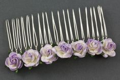 The Tea Rose Comb is a pretty hair accessory, perfect for a summer wedding. It features a row of delightful small parchment roses. Available on two sizes of comb. Available in a fabulous range of roses.